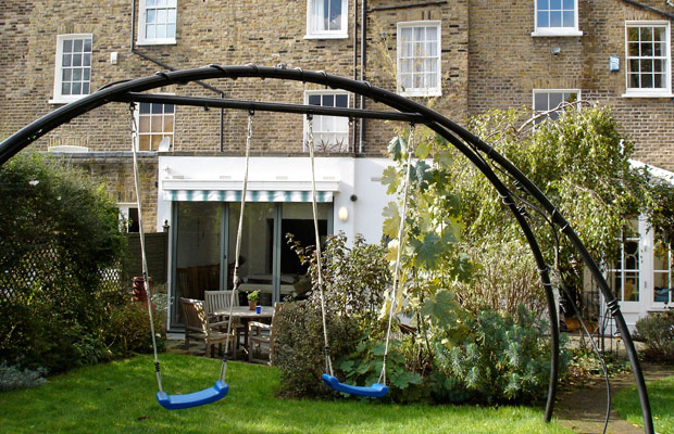 Bespoke ornamental arch converts to swings for the children - Carol Whitehead garden design