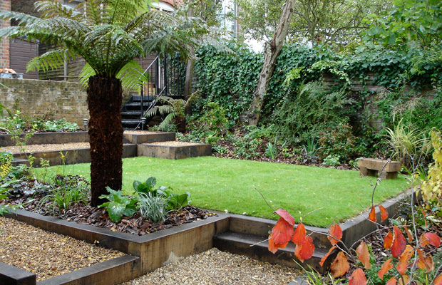 Tree ferns, wooden sleepers and gravel path solve a shady sloping garden - Carol Whitehead garden design