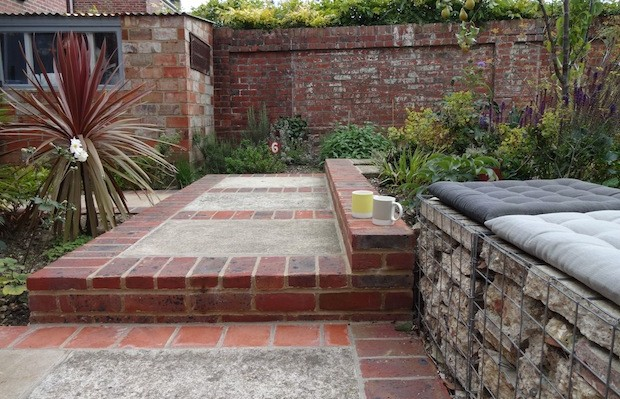 Gabbion seats on recycled concrete patio with red brick edge - Carol Whitehead garden design