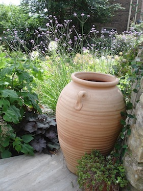 terracotta urn on terrace near stone wall with planting behind