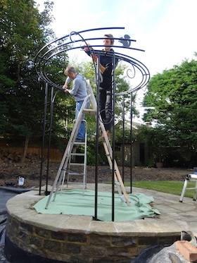two people install metal arbour adjacent to a pond