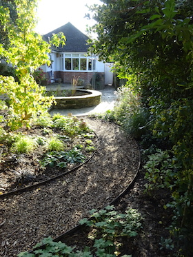 curved path from raised circular pond view from back of garden