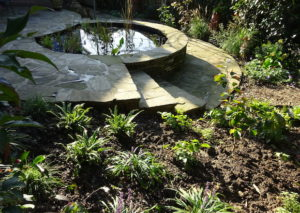 a low impact garden design with retaining wall pond for wildlife