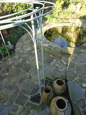 metal pergola over recycled York stone patio next to wildlife pond